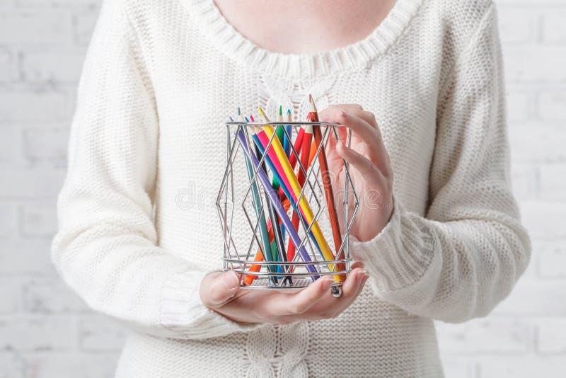 Main retenant un bidon avec des crayons de couleur images stock