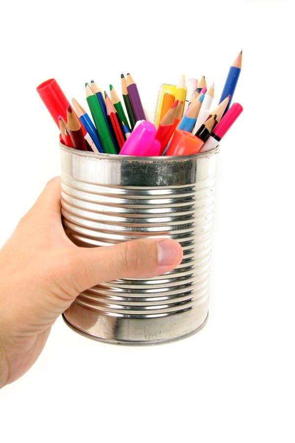 Main retenant un bidon avec des crayons de couleur photographie stock libre de droits