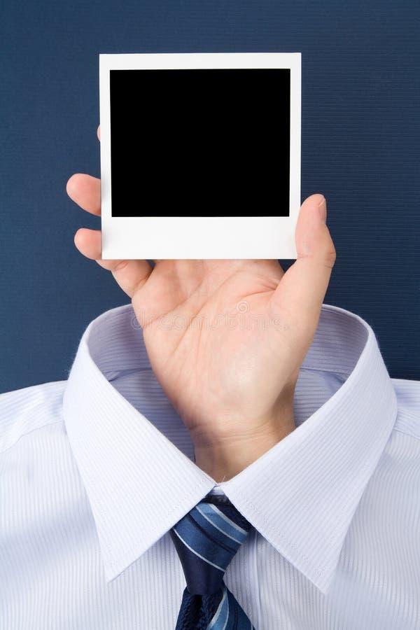 Main retenant une photo blanc photographie stock