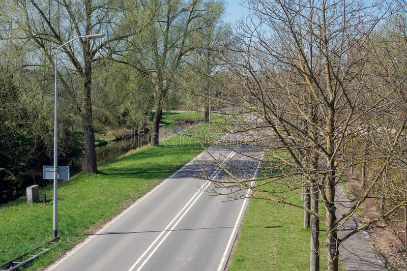 Main road in Lelystad, capital city of Dutch province Flevoland. Major road in early springtime along park and ditch in Lelystad, capital city of Dutch province royalty free stock photos