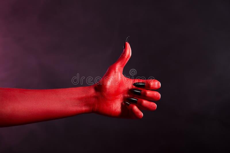 Main rouge de diable de peau montrant des pouces  images libres de droits