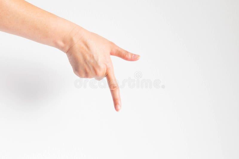 Main se dirigeant en bas en bas de la direction sur le fond blanc image stock
