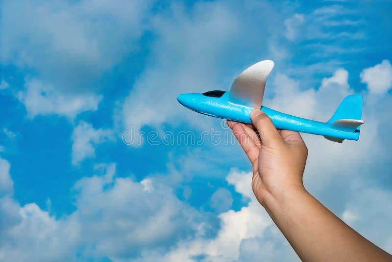Main se soulevant vers le haut d'un modèle bleu d'avion images libres de droits