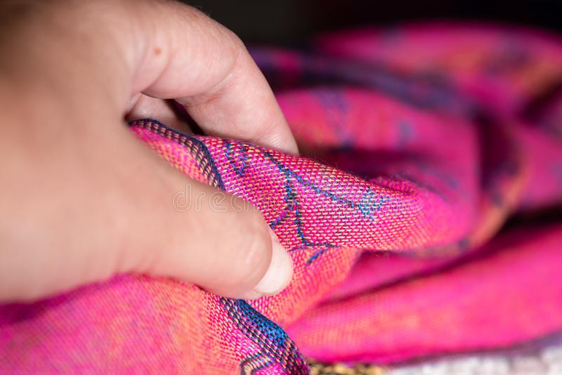 Main soflty touchant un tissu rose de cachemire image stock