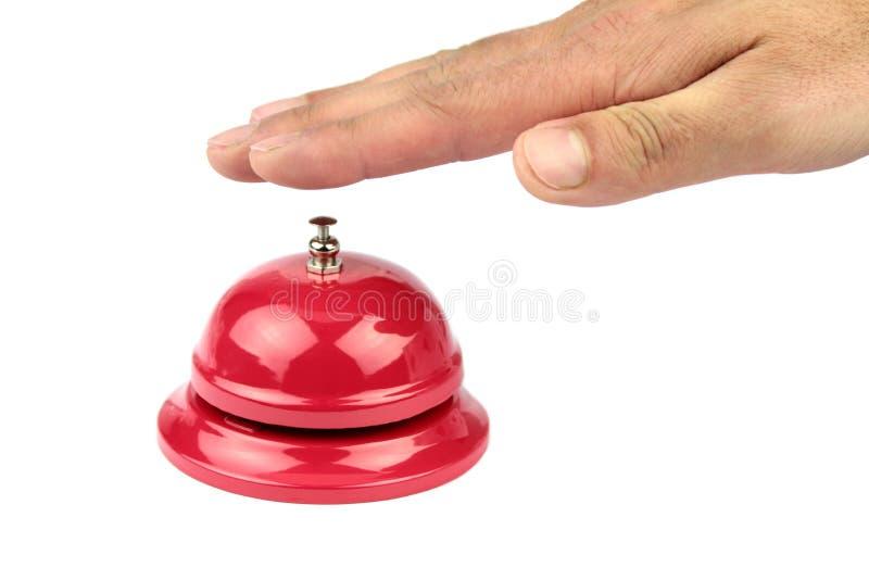 Main sonnant dans la cloche rouge de service image libre de droits