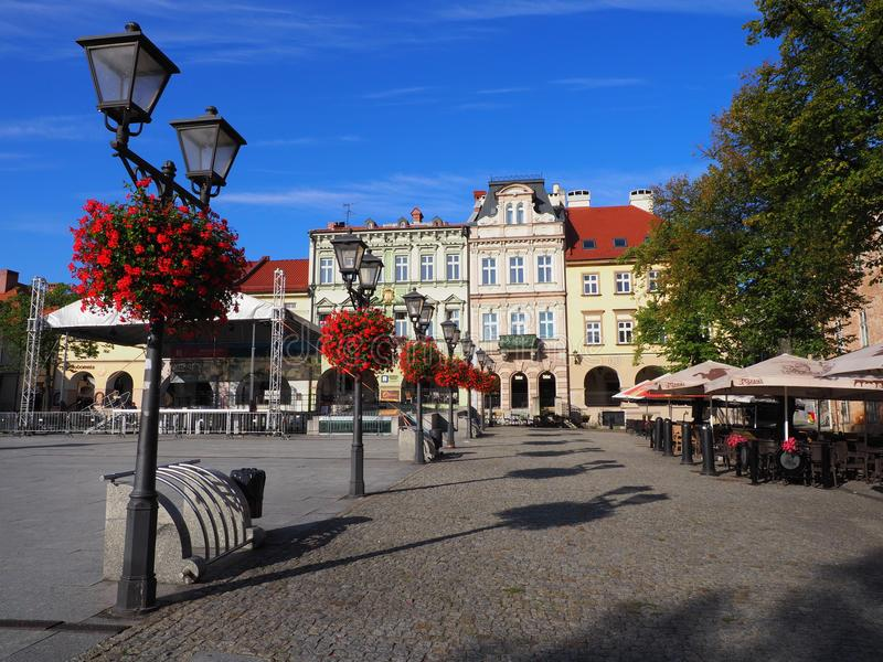Main square in historical city center of Bielsko-Biala in POLAND with colorful old buildings, street lamps, red flowers. stock image