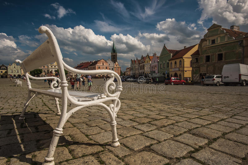 Main square in Telc, a town in Moravia with the famous 16th-century houses, Czech republic. Focus on amazing old white bench, Unes royalty free stock photography