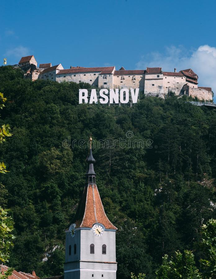 Main street of ancient Saxon town on bright sunny day. Fortified church and medieval castle on the hill. Location Rasnov,. Transylvania, Romania. Picturesque royalty free stock photo