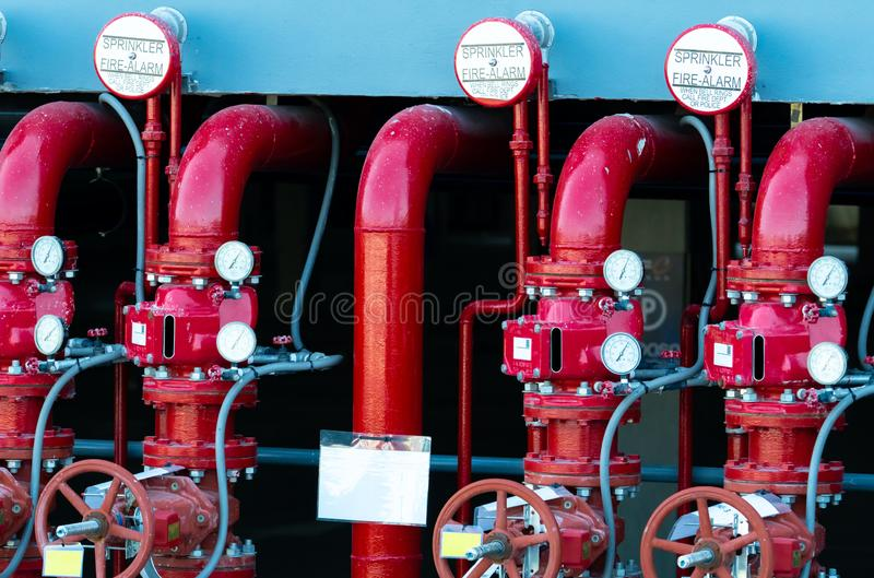 Main supply water piping in the fire extinguishing system. Fire sprinkler system with red pipes. Fire suppression. Manual valve stock photos