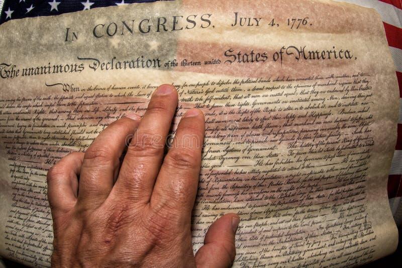 Main sur la déclaration d'indépendance le 4 juillet 1776 sur le drapeau des Etats-Unis photo libre de droits
