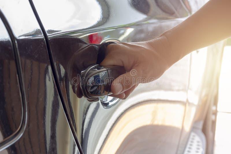 Main sur la fin de poignée de la portière de voiture d'ouverture de main de l'homme photo stock