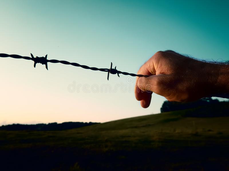 Main sur le barbelé contre le ciel bleu Le concept de la liberté et de la prison photos stock