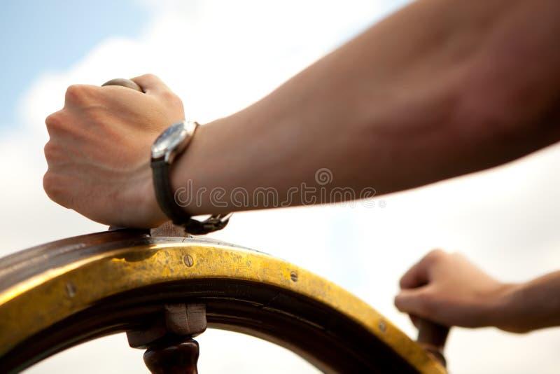 Main sur le gouvernail de direction de bateau. images stock