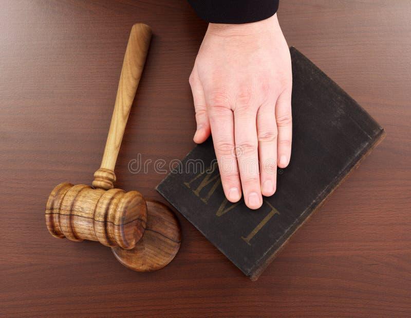 Main sur le livre et le marteau de loi image libre de droits
