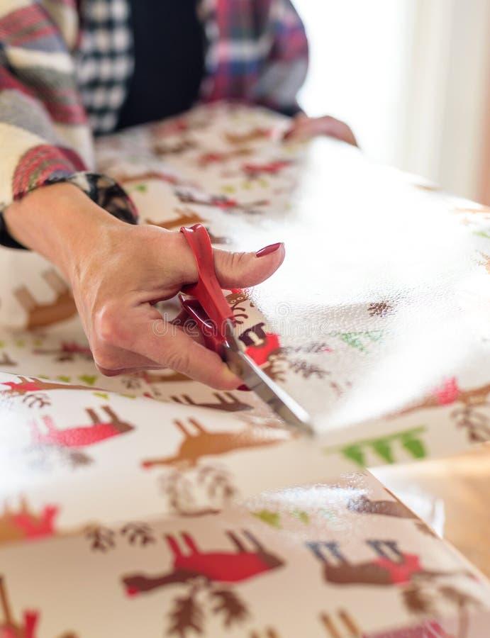 Main tenant des ciseaux enveloppant des cadeaux de Noël images libres de droits