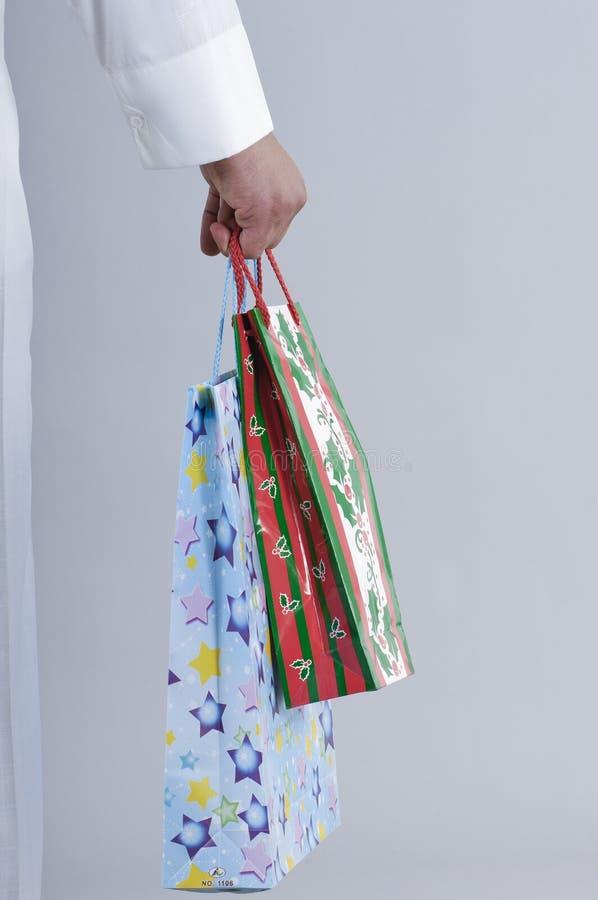 Main tenant des paniers avec des cadeaux photos stock