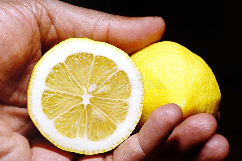 Main tenant deux moitiés d'un citron photos libres de droits