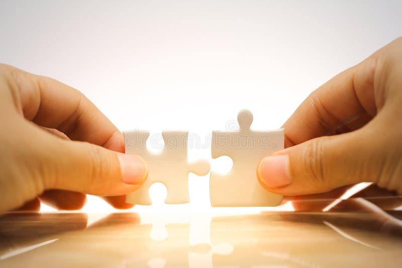 Main tenant et reliant des puzzles denteux image stock