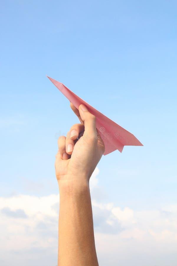 Main tenant l'avion de papier rose photographie stock