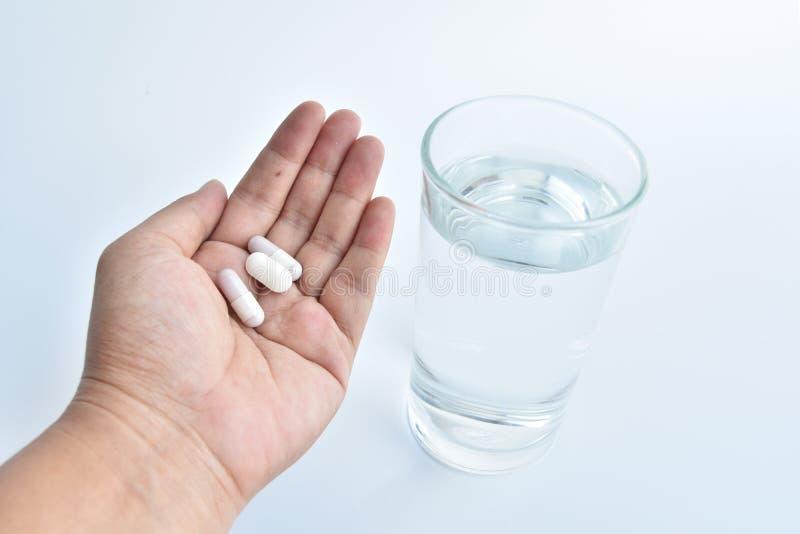 main tenant l'eau de médecine et en verre images stock