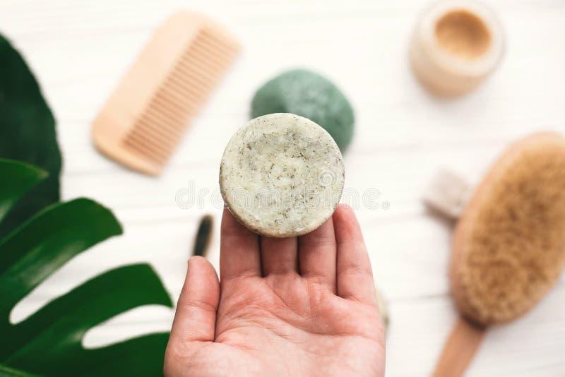 Main tenant la barre solide naturelle de shampooing sur le fond de b en bambou photos libres de droits