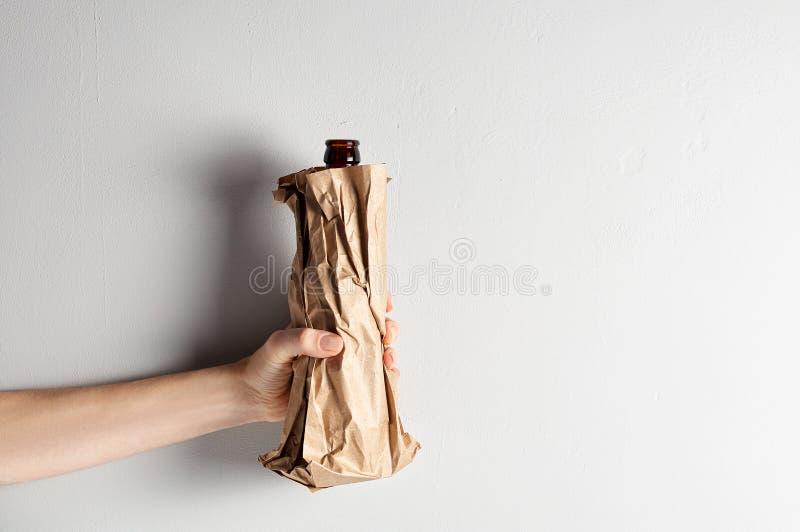Main tenant la bouteille à bière dans le sac de papier sur le fond gris image stock