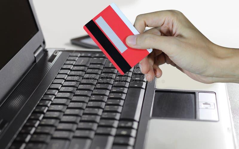 Main tenant la carte de crédit et à l'aide de l'ordinateur portable, concept de achat en ligne images libres de droits