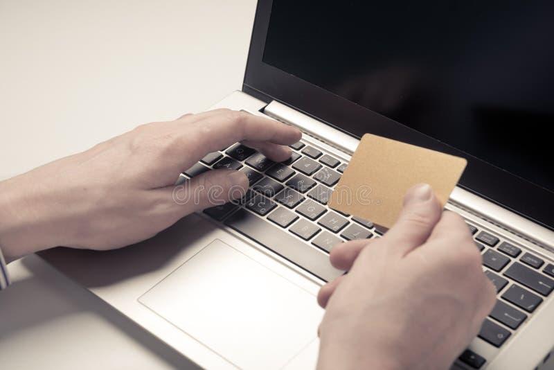 Main tenant la carte de crédit et l'ordinateur portable d'utilisation photos libres de droits