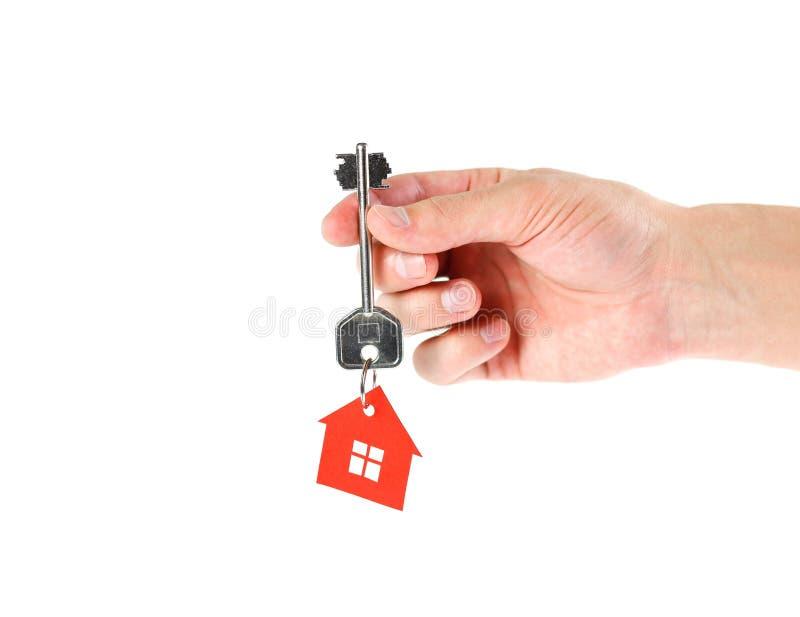 Main tenant la clé sur la maison Fin vers le haut d'isolement sur b blanc photos libres de droits