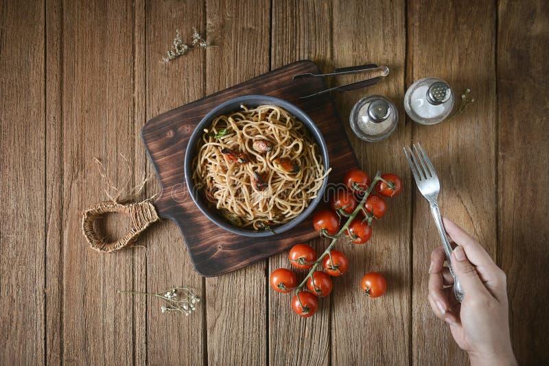 Main tenant la fourchette avec les pâtes, la moule, la tomate et la garniture italiennes de spaghetti sur le plat rond et le plat images libres de droits