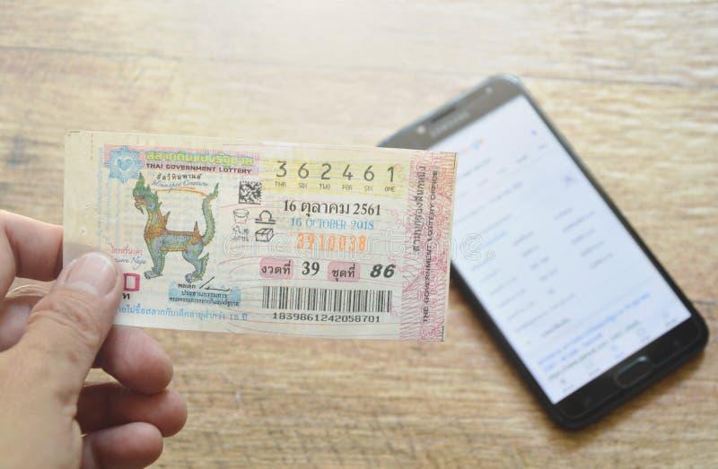 main tenant la loterie thaïlandaise de gouvernement et vérifiant des résultats de site Web au téléphone intelligent photographie stock libre de droits