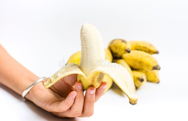Main tenant la petite banane tropicale sur le blanc photographie stock