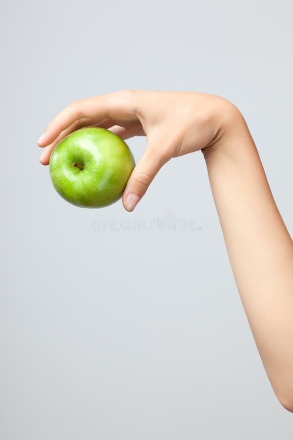 Main tenant la pomme. image stock
