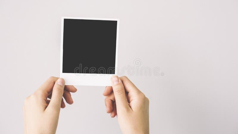 Main tenant le cadre vide de photo image stock