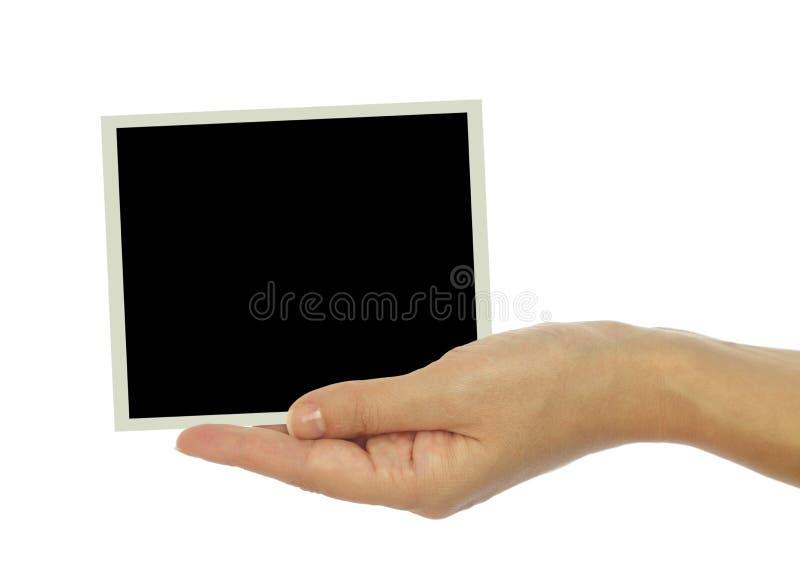 Main tenant le cadre vide de photo image libre de droits