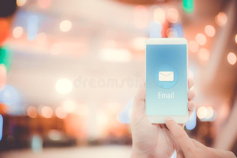 Main tenant le contrôle d'homme et envoyant le message avec l'email dans un téléphone sur le fond de bokeh photographie stock