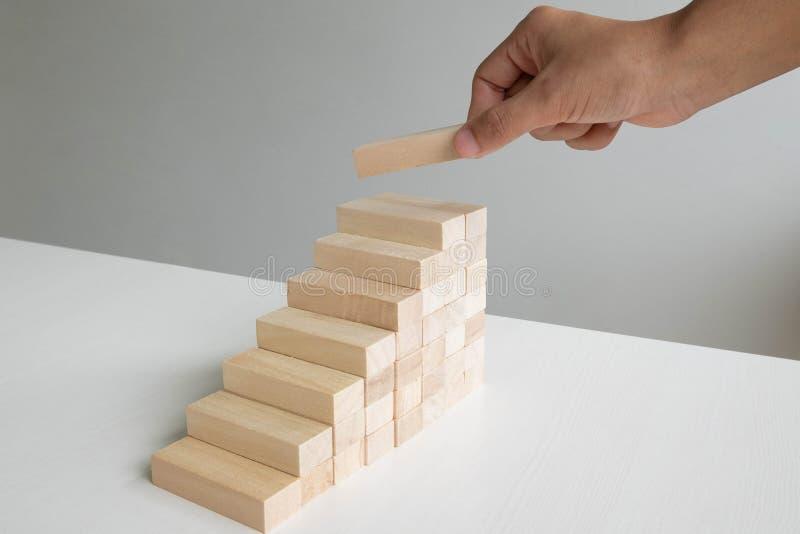 Main tenant le jeu en bois de blocs, le risque de concept de plan de gestion et de stratégie, le processus de réussite commercial images libres de droits