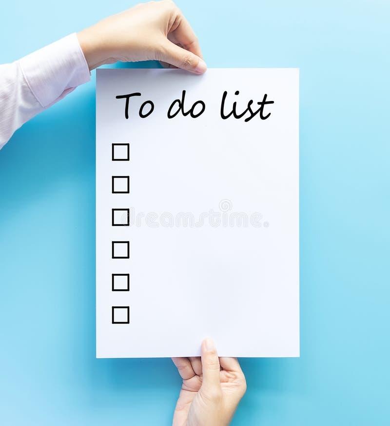 Main tenant le papier avec pour faire le texte tiré de liste et de checkbox à la main d'isolement sur le concept bleu de fond, de photo stock
