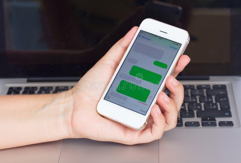 Main tenant le smartphone avec des nuages de sms image stock