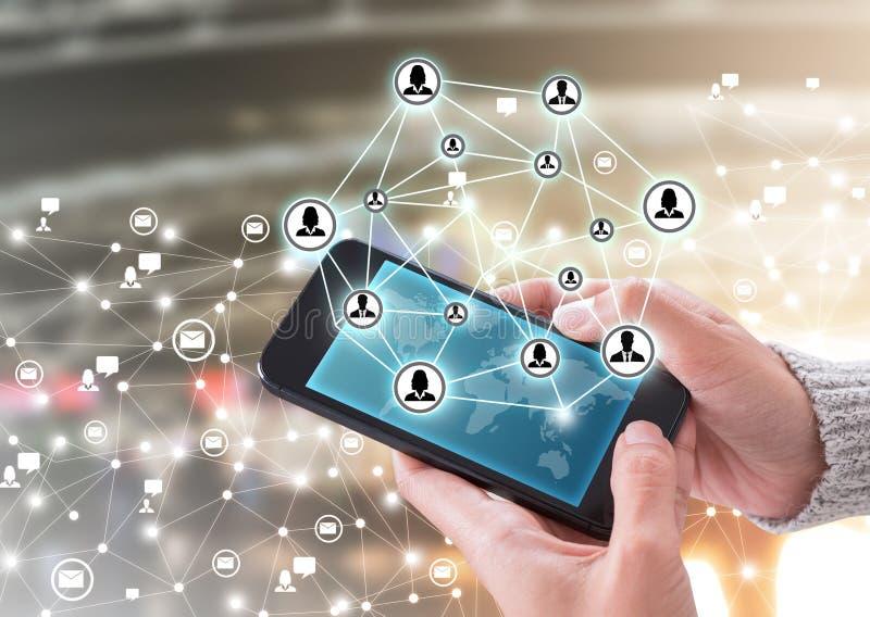Main tenant le smartphone et la technologie des communications moderne photo stock