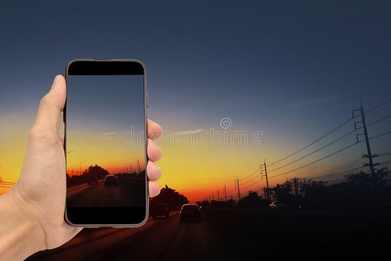 Main tenant le smartphone sur la voiture image libre de droits