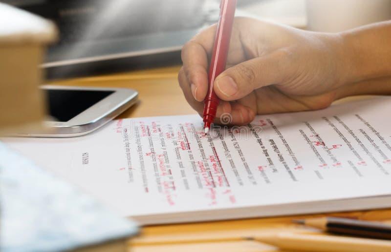 Main tenant le stylo rouge au-dessus de corriger sur épreuves le texte photo stock