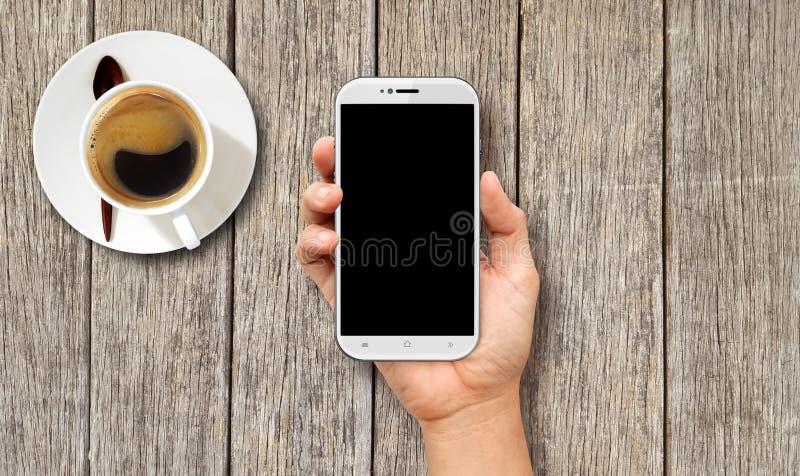 Main tenant le téléphone intelligent blanc sur la table basse en bois images stock