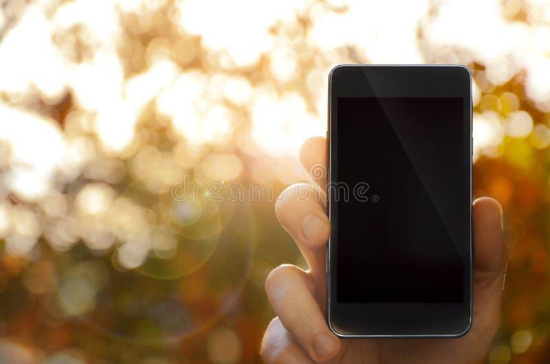 Main tenant le téléphone intelligent, fond brouillé photo stock