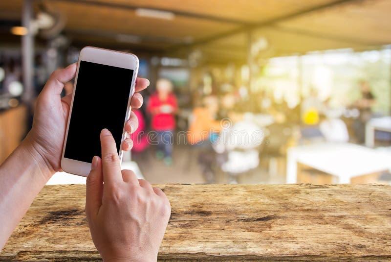 Main tenant le téléphone intelligent mobile avec le fond de tache floue de café image libre de droits