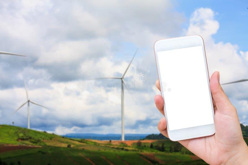 Main tenant le téléphone portable avec le fond de turbines de vent images libres de droits