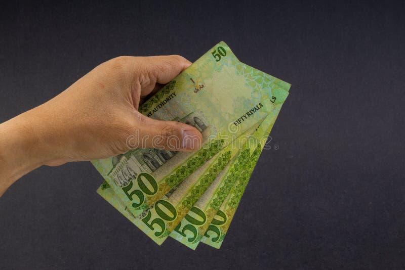 Main tenant les billets de banque saoudiens de riyal sur le fond noir photos libres de droits