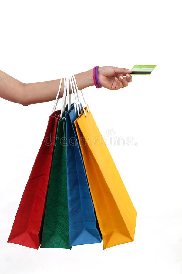 Main tenant les paniers et la carte de crédit image libre de droits