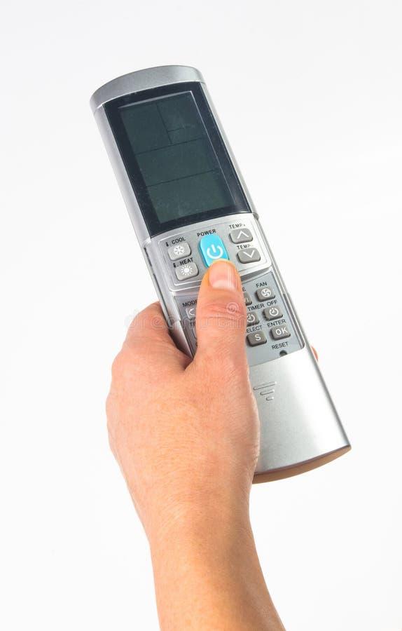 main tenant un à télécommande sur le fond blanc, en gros plan image libre de droits