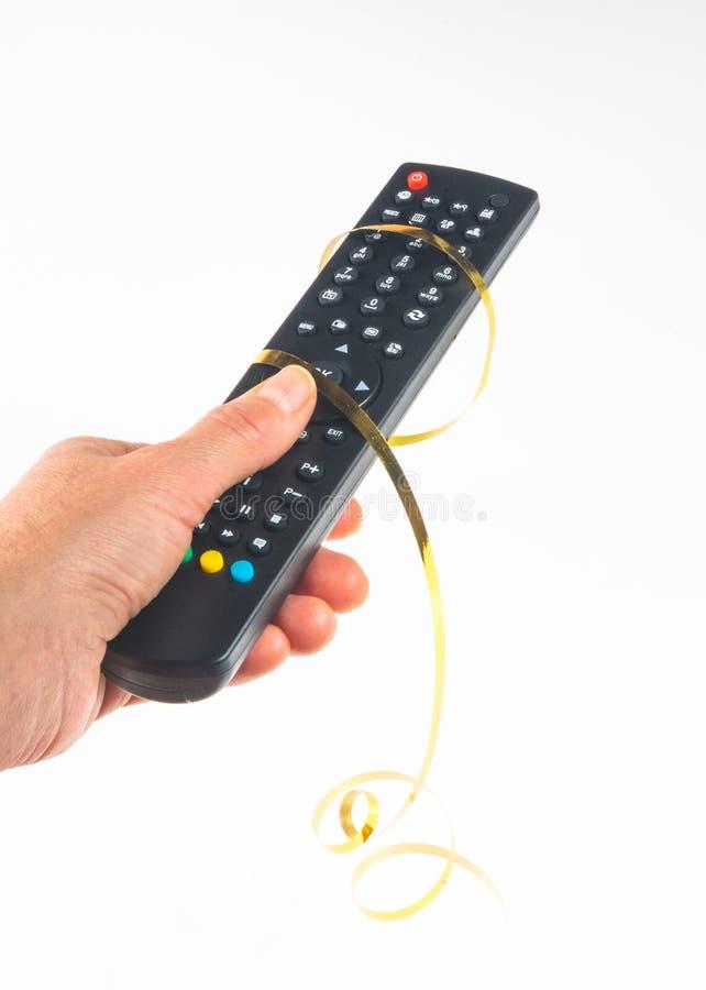 main tenant un à télécommande sur le fond blanc, en gros plan image stock